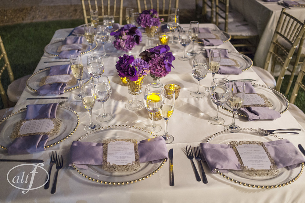 Square wedding tables with lavender napkins and dark purple centerpieces. Pre-wedding photos of the bride and the groom, without seeing each other. Las Vegas Wedding Planner Andrea Eppolito.  Image by Altf.com.