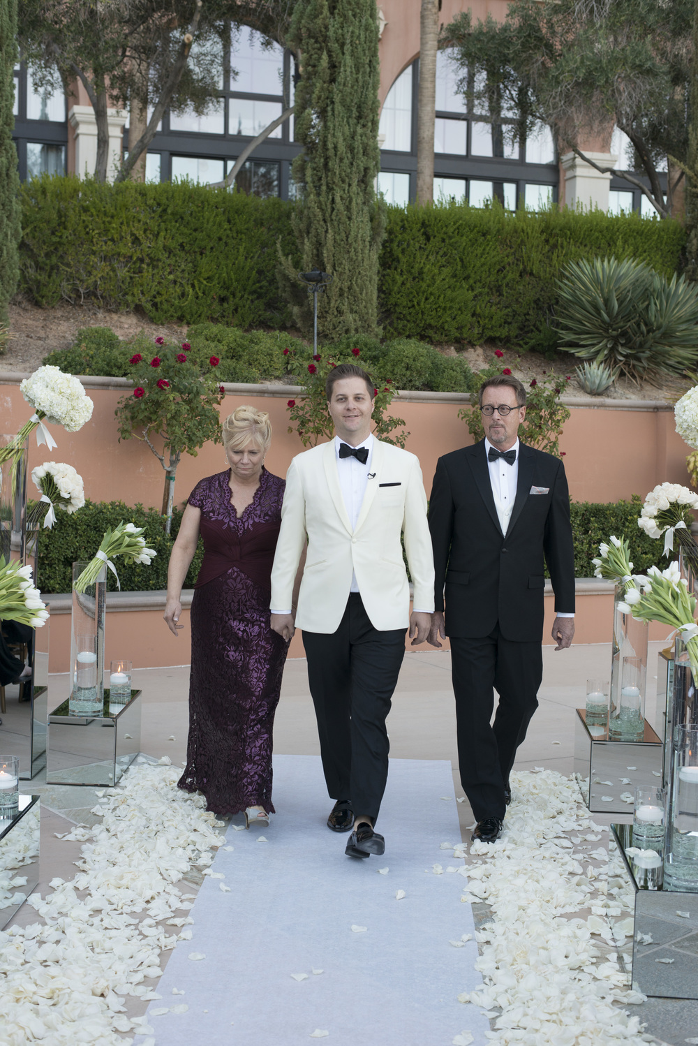 Groom is escorted by his mother and father.  Vendor Credits: Las Vegas Wedding Planner:  Andrea Eppolito Events  | Venue: The Westin Lake Las Vegas  |  Floral & Decor:  Flora Couture |  Photography:  Altf Photography  |  Videography: Something New Films  | Wedding Cake:  Peridot Sweets  |  Beauty by:  Make Up in the 702  |  Wedding Gown: P'Nina Tornai  |  Veil: Kleinfeld New York  |  Shoes:  Christian Louboutin  |  Tuxedo:  Men's Warehouse