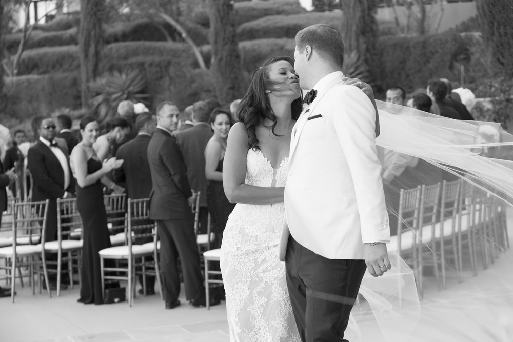 Black and White Photo of bride and groom kissing at Lake Las Vegas. Veil in the wind.   Vendor Credits: Las Vegas Wedding Planner:  Andrea Eppolito Events  | Venue: The Westin Lake Las Vegas  |  Floral & Decor:  Flora Couture |  Photography:  Altf Photography  |  Videography: Something New Films  | Wedding Cake:  Peridot Sweets  |  Beauty by:  Make Up in the 702  |  Wedding Gown: P'Nina Tornai  |  Veil: Kleinfeld New York  |  Shoes:  Christian Louboutin  |  Tuxedo:  Men's Warehouse