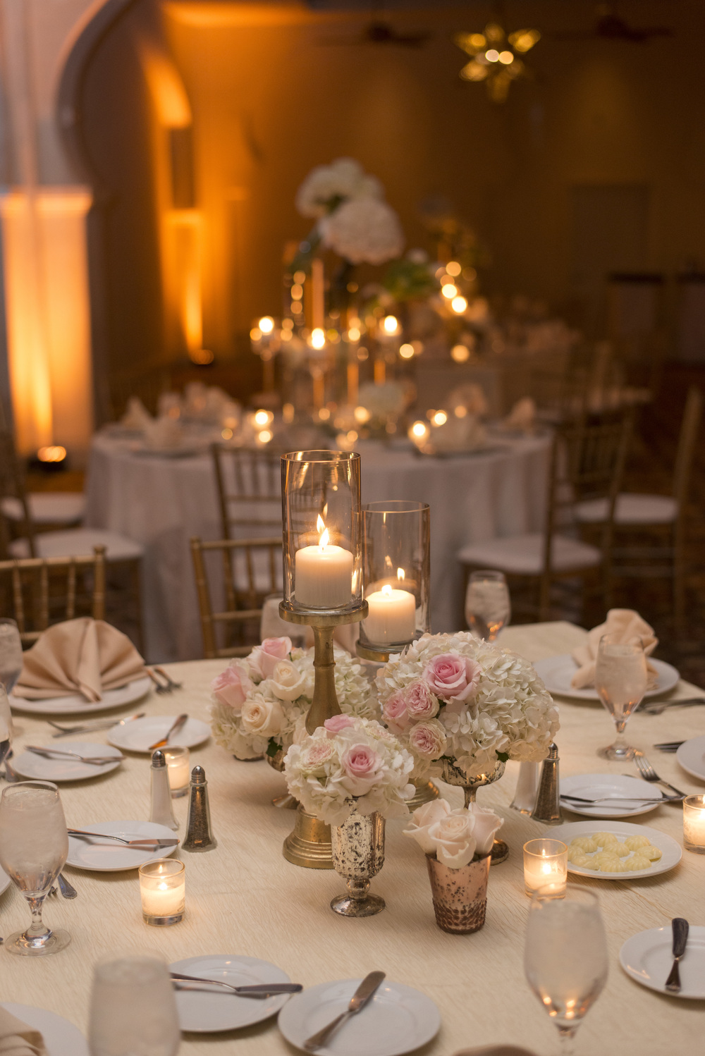 Low pink and white centerpieces with candles.  Vendor Credits: Las Vegas Wedding Planner:  Andrea Eppolito Events  | Venue: The Westin Lake Las Vegas  |  Floral & Decor:  Flora Couture |  Photography:  Altf Photography  |  Videography: Something New Films  | Wedding Cake:  Peridot Sweets  |  Beauty by:  Make Up in the 702  |  Wedding Gown: P'Nina Tornai  |  Veil: Kleinfeld New York  |  Shoes:  Christian Louboutin  |  Tuxedo:  Men's Warehouse