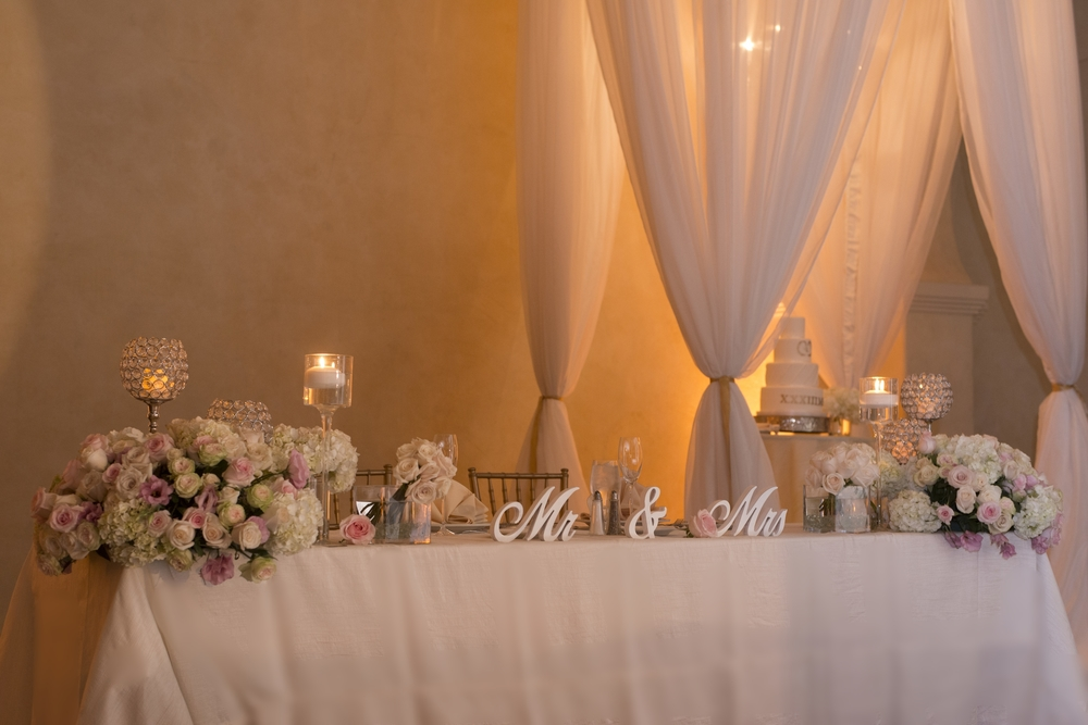 Sweetheart table with Mr. and Mrs. Signs and pink and ivory candles.  Vendor Credits: Las Vegas Wedding Planner:  Andrea Eppolito Events  | Venue: The Westin Lake Las Vegas  |  Floral & Decor:  Flora Couture |  Photography:  Altf Photography  |  Videography: Something New Films  | Wedding Cake:  Peridot Sweets  |  Beauty by:  Make Up in the 702  |  Wedding Gown: P'Nina Tornai  |  Veil: Kleinfeld New York  |  Shoes:  Christian Louboutin  |  Tuxedo:  Men's Warehouse