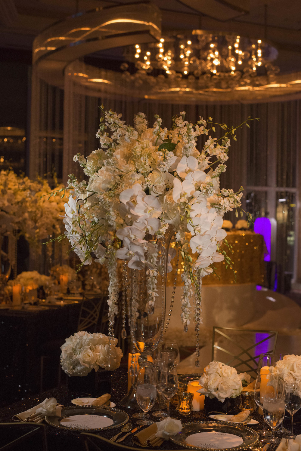 Lush white centerpieces with orchids and roses.  Credits:  Wedding Planning and Event Design by  Andrea Eppolito Events  Luxury Las Vegas Wedding held at  The Mandarin Oriental .  Florals and Decor handled by  Destinations by Design .  Photography by  AltF Photography .  Wedding Film and Videography by  Pure Light Creative  with Music and Entertainment by  Mike Fox & Company .  Hair and Make Up by  Your Beauty Call .  Photo Booth and Video Screen by  The Joy Squad .    Stationery by  Laura Damiano Designs .