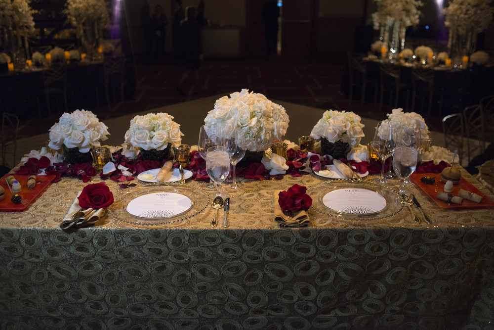 Sweetheart table with gold linen and red rose accents.  Credits:  Wedding Planning and Event Design by  Andrea Eppolito Events  Luxury Las Vegas Wedding held at  The Mandarin Oriental .  Florals and Decor handled by  Destinations by Design .  Photography by  AltF Photography .  Wedding Film and Videography by  Pure Light Creative  with Music and Entertainment by  Mike Fox & Company .  Hair and Make Up by  Your Beauty Call .  Photo Booth and Video Screen by  The Joy Squad .    Stationery by  Laura Damiano Designs .
