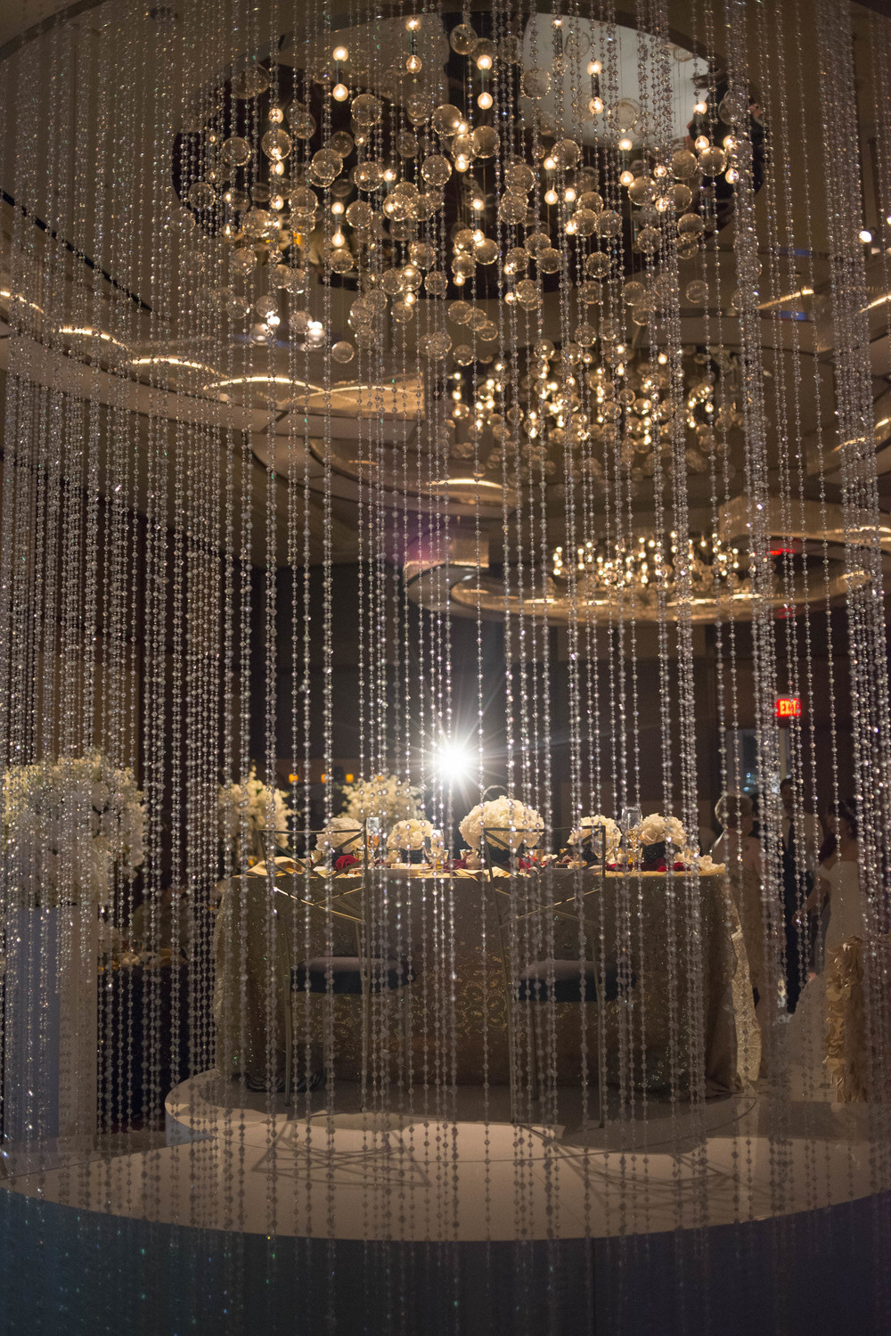 Sweetheart table seen through the crystal drape. Credits:  Wedding Planning and Event Design by  Andrea Eppolito Events  Luxury Las Vegas Wedding held at  The Mandarin Oriental .  Florals and Decor handled by  Destinations by Design .  Photography by  AltF Photography .  Wedding Film and Videography by  Pure Light Creative  with Music and Entertainment by  Mike Fox & Company .  Hair and Make Up by  Your Beauty Call .  Photo Booth and Video Screen by  The Joy Squad .    Stationery by  Laura Damiano Designs .