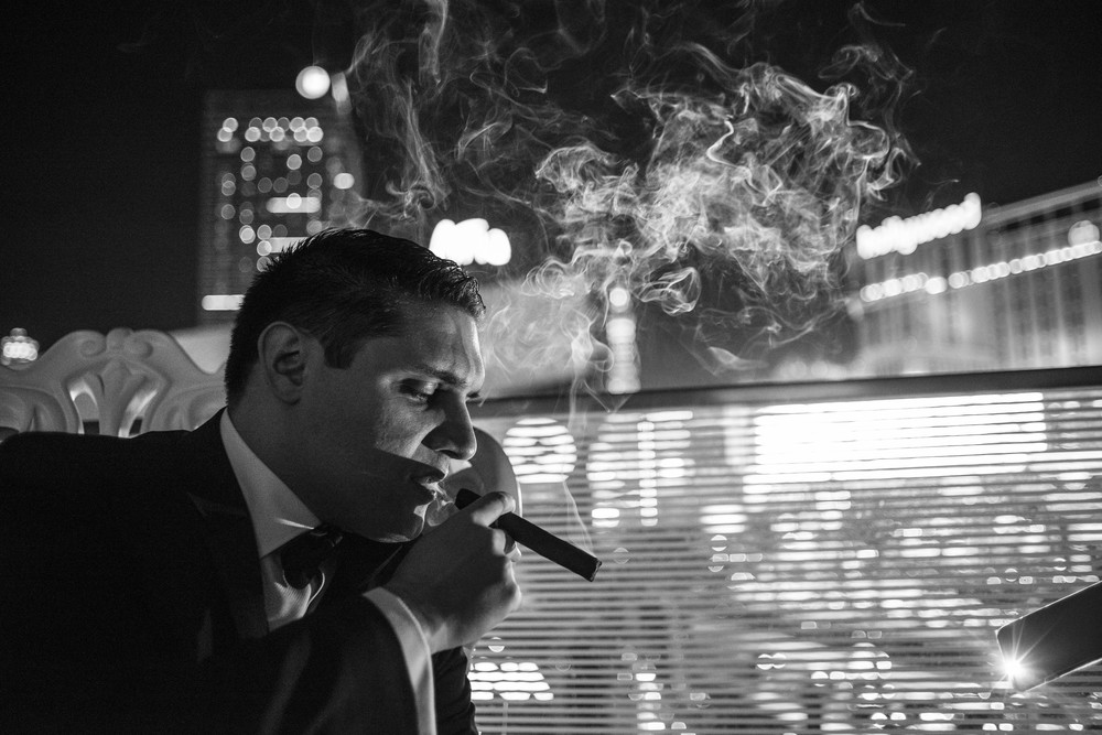 Groom enjoys a cigar on the patio of the Mandarin Oriental.   Credits:  Wedding Planning and Event Design by  Andrea Eppolito Events  Luxury Las Vegas Wedding held at  The Mandarin Oriental .  Florals and Decor handled by  Destinations by Design .  Photography by  AltF Photography .  Wedding Film and Videography by  Pure Light Creative  with Music and Entertainment by  Mike Fox & Company .  Hair and Make Up by  Your Beauty Call .  Photo Booth and Video Screen by  The Joy Squad .    Stationery by  Laura Damiano Designs .