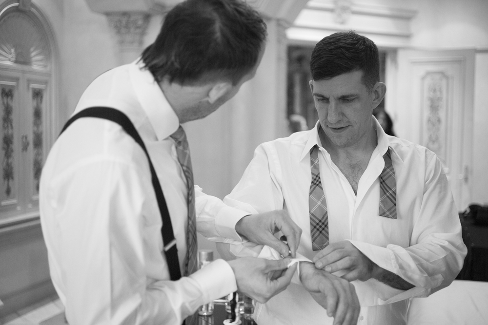 Two grooms get dressed together before their same sex wedding in Las Vegas.   Venue -   The Westgate    |    Las Vegas Wedding Planner & Event Design by   Andrea Eppolito    |    Photography by   AltF Photography    |    Videography by   Something New Films    |    Floral and Decor by   DBD Vegas    |    Live Art by   The Girl Who Drew You    |    Stationery by   Paper & Home
