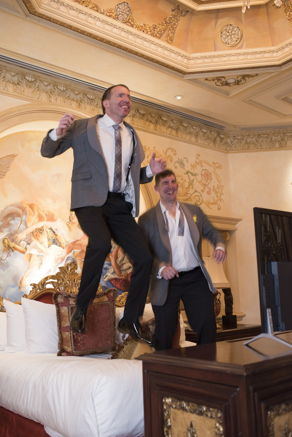 Two grooms jump on a bed.   Newlyweds Brian Sauls and Chris Mancini at their same-sex wedding in Las Vegas.  The vintage Vegas themed event was hosted in the Verona Suite of The Westgate.   Venue -  The Westgate   |  Las Vegas Wedding Planner & Event Design by  Andrea Eppolito   |  Photography by  AltF Photography   |  Videography by  Something New Films   |  Floral and Decor by  DBD Vegas   |  Live Art by  The Girl Who Drew You   |  Stationery by  Paper & Home
