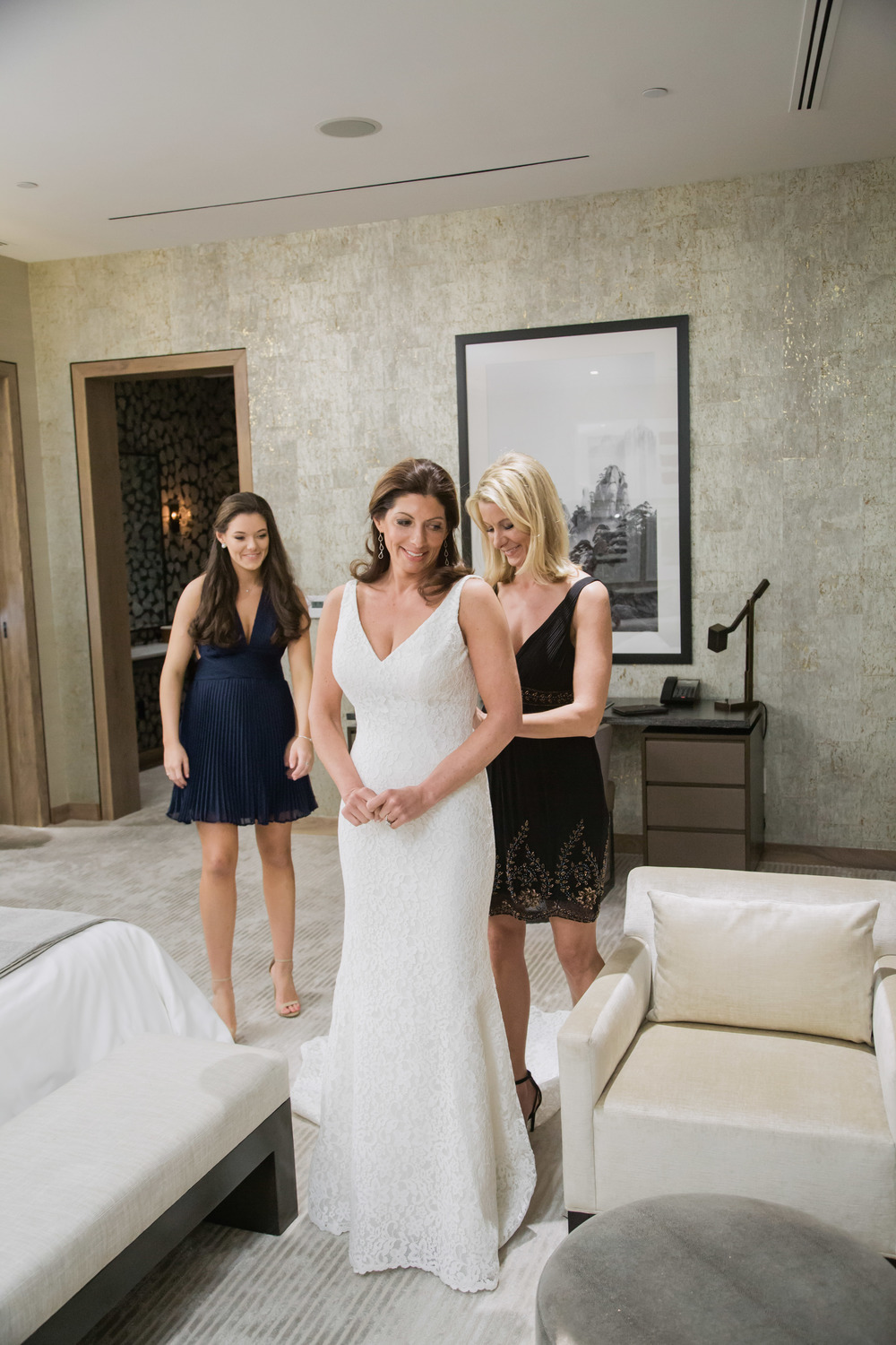 The bride dressed by her daughter and best friend.  Vendor Credits:  Wedding in the  Nobu Villa   |  Las Vegas Wedding Planner  Andrea Eppolito    |  Photography by  Adam Frazier   |  Videography by  Pure Light Creative   |  Floral and Decor by  Destinations by Design   |  Lighting by LED Unplugged  |  Music by  DJ Mike Fox