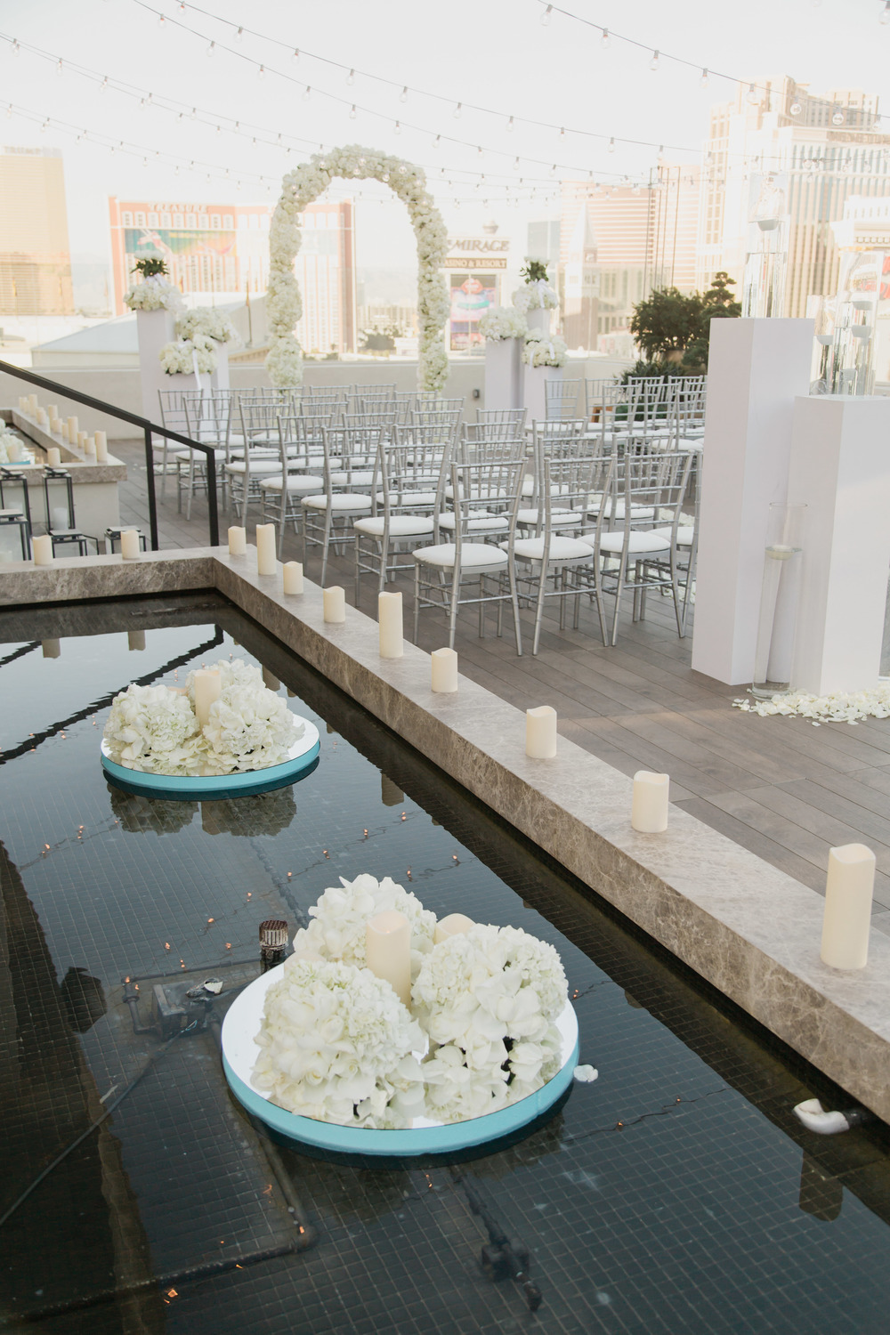 White flowers floating in the water feature on a patio of Caesars Palace. Vendor Credits:  Wedding in the  Nobu Villa   |  Las Vegas Wedding Planner  Andrea Eppolito    |  Photography by  Adam Frazier   |  Videography by  Pure Light Creative   |  Floral and Decor by  Destinations by Design   |  Lighting by LED Unplugged  |  Music by  DJ Mike Fox
