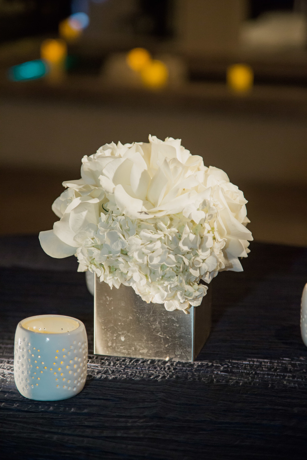 White flowers and white centerpieces on dark blue linens.   Vendor Credits:    Wedding in the   Nobu Villa    |    Las Vegas Wedding Planner   Andrea Eppolito     |    Photography by   Adam Frazier    |    Videography by   Pure Light Creative    |    Floral and Decor by   Destinations by Design    |  Lighting by LED Unplugged  |    Music by   DJ Mike Fox