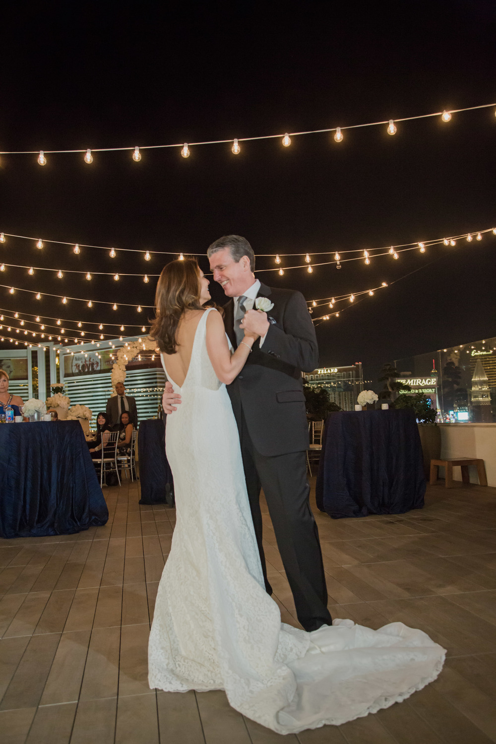 The first dance beneath the starts and bistro lights.   White flowers and white centerpieces on dark blue linens.   Vendor Credits:    Wedding in the   Nobu Villa    |    Las Vegas Wedding Planner   Andrea Eppolito     |    Photography by   Adam Frazier    |    Videography by   Pure Light Creative    |    Floral and Decor by   Destinations by Design    |  Lighting by LED Unplugged  |    Music by   DJ Mike Fox