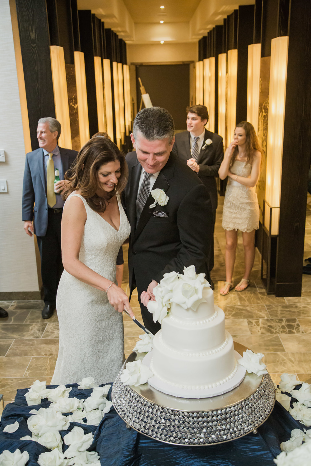Cutting the cake.  White flowers and white centerpieces on dark blue linens.   Vendor Credits:    Wedding in the   Nobu Villa    |    Las Vegas Wedding Planner   Andrea Eppolito     |    Photography by   Adam Frazier    |    Videography by   Pure Light Creative    |    Floral and Decor by   Destinations by Design    |  Lighting by LED Unplugged  |    Music by   DJ Mike Fox