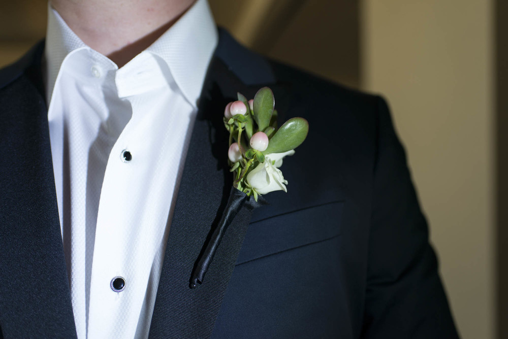 Rose and berry boutonniere by DBD Vegas.  Gay Wedding at Red Rock Resort by Las Vegas Wedding Planner Andrea Eppolito.  Images by Altf Photography.  Florals and decor by Destinations by Design.  Two grooms at a gay wedding in Las Vegas.