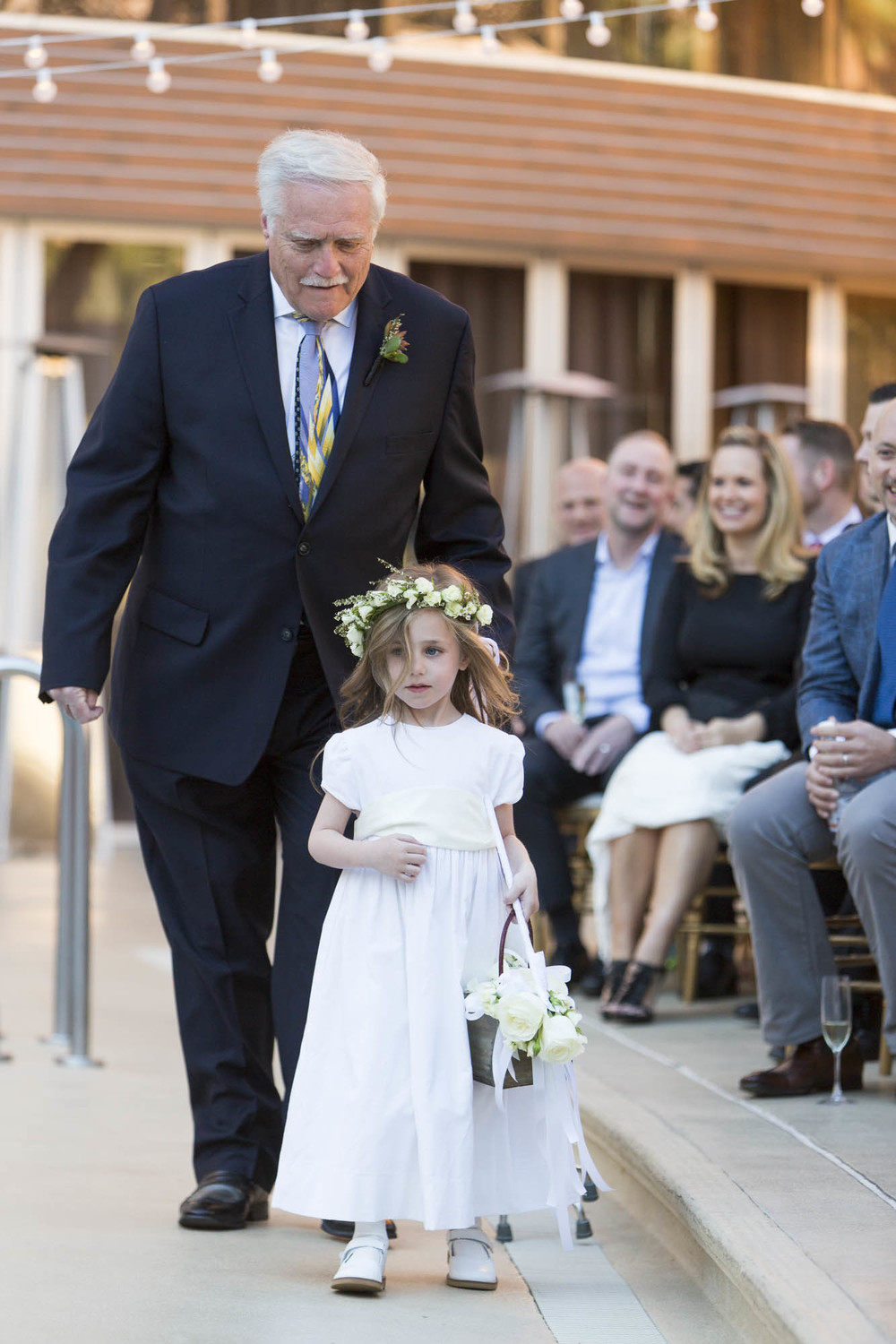 Daughter of the grooms being walked down the aisle by her Grandpa. Gay Wedding at Red Rock Resort by Las Vegas Wedding Planner Andrea Eppolito.  Images by Altf Photography.  Florals and decor by Destinations by Design.  Two grooms at a gay wedding in Las Vegas.