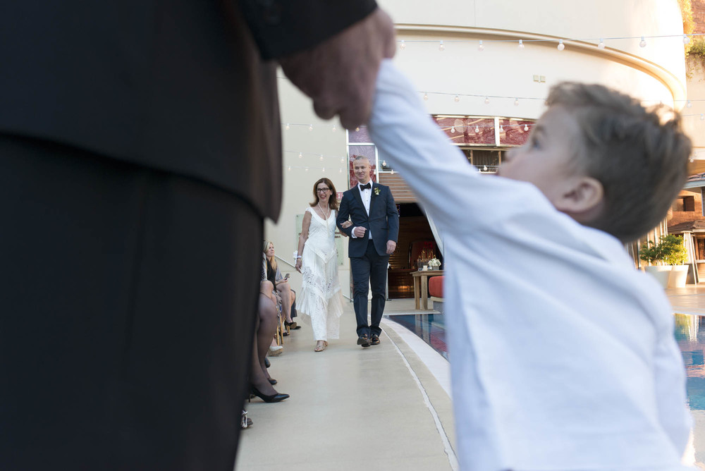 Love this photo of the groom looking at his son as he walks down the aisle. Gay Wedding at Red Rock Resort by Las Vegas Wedding Planner Andrea Eppolito.  Images by Altf Photography.  Florals and decor by Destinations by Design.  Two grooms at a gay wedding in Las Vegas.