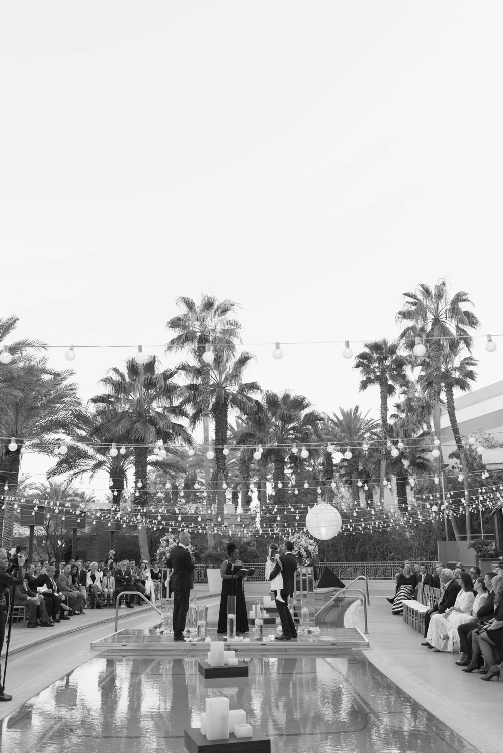 Gay wedding ceremony shot in black and white at Cherry Crimson at Red Rock. Gay Wedding at Red Rock Resort by Las Vegas Wedding Planner Andrea Eppolito.  Images by Altf Photography.  Florals and decor by Destinations by Design.  Two grooms at a gay wedding in Las Vegas.
