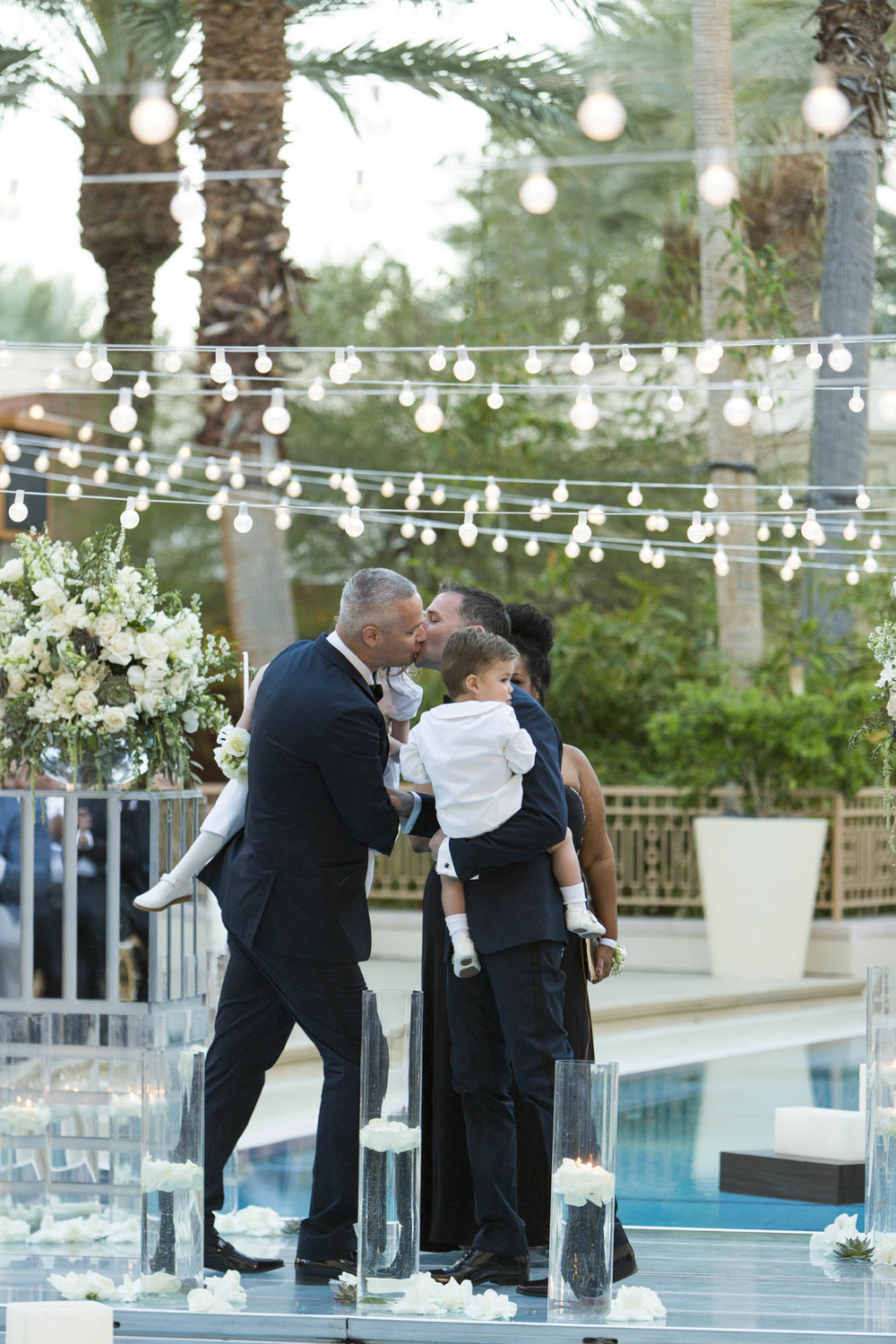 The first kiss.  Gay Wedding at Red Rock Resort by Las Vegas Wedding Planner Andrea Eppolito.  Images by Altf Photography.  Florals and decor by Destinations by Design.  Two grooms at a gay wedding in Las Vegas.