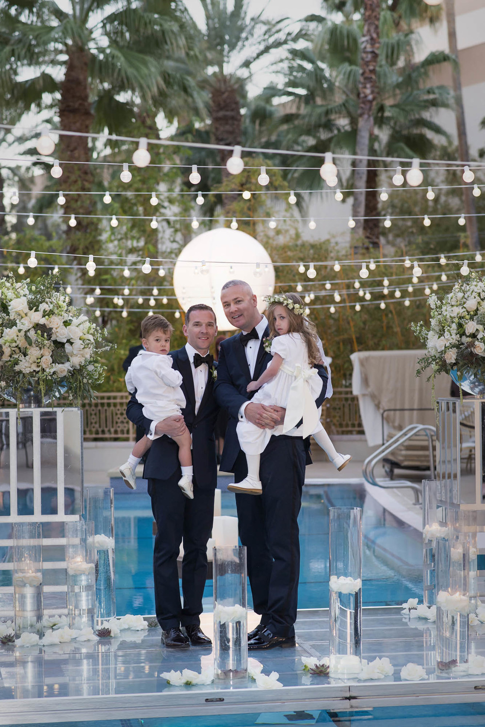 Family portrait of the two dads with their children on the day of their wedding. Gay Wedding at Red Rock Resort by Las Vegas Wedding Planner Andrea Eppolito.  Images by Altf Photography.  Florals and decor by Destinations by Design.  Two grooms at a gay wedding in Las Vegas.
