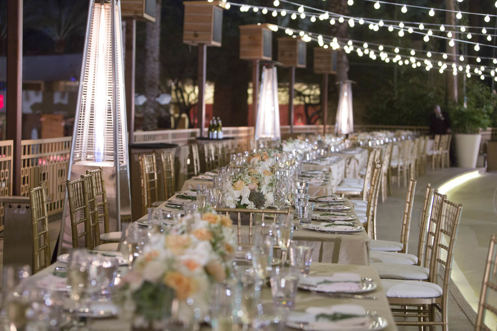 Long winding table with beige linens, succulents, and peach roses. Gay Wedding at Red Rock Resort by Las Vegas Wedding Planner Andrea Eppolito.  Images by Altf Photography.  Florals and decor by Destinations by Design.  Two grooms at a gay wedding in Las Vegas.