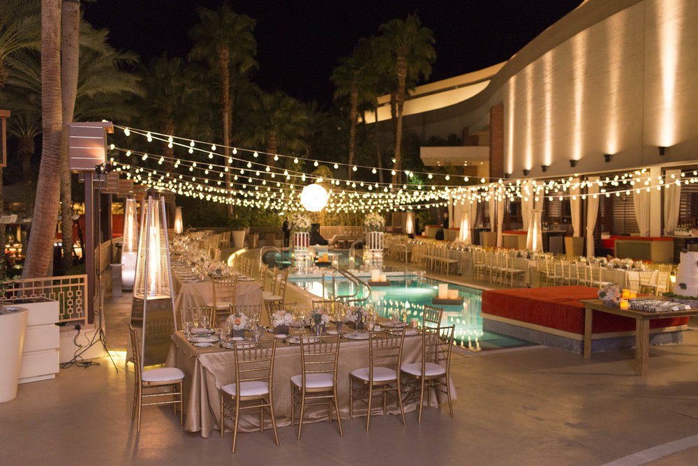 Bistro Lighting over a pool with floating candles, gold chiavari chairs, and gold linens.  Glam rustic decor.  Gay Wedding at Red Rock Resort by Las Vegas Wedding Planner Andrea Eppolito.  Images by Altf Photography.  Florals and decor by Destinations by Design.  Two grooms at a gay wedding in Las Vegas.