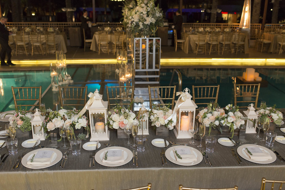 Head table with White lanterns, succulents, ivory and peach roses.  Gay Wedding at Red Rock Resort by Las Vegas Wedding Planner Andrea Eppolito.  Images by Altf Photography.  Florals and decor by Destinations by Design.  Two grooms at a gay wedding in Las Vegas.