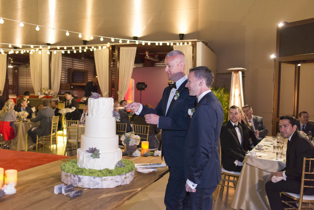 The grooms cut a simple white cake on a wooden base with succulent accents. Gay Wedding at Red Rock Resort by Las Vegas Wedding Planner Andrea Eppolito.  Images by Altf Photography.  Florals and decor by Destinations by Design.  Two grooms at a gay wedding in Las Vegas.