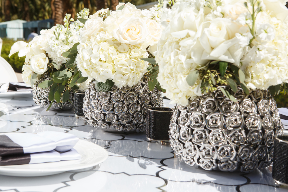 Keeping a neutral palette of white and black allows the design and textured metal vases to stand out.