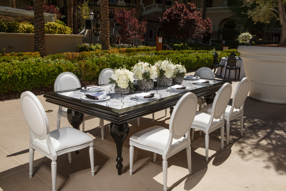 A black table with white lacquered chairs are a surprisingly beautiful set up for an outdoor luncheon.