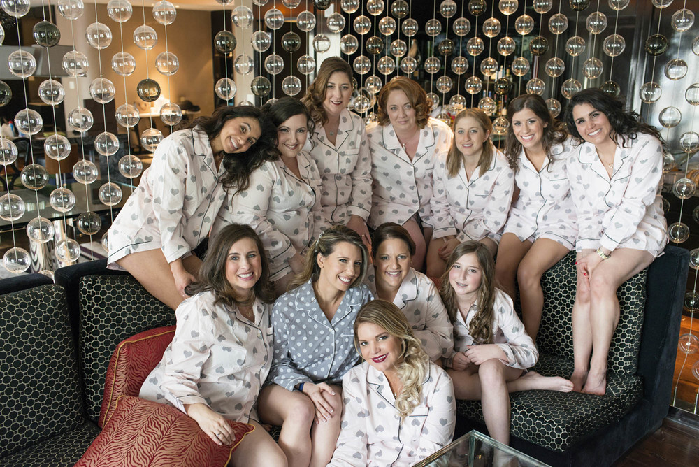 Bridesmaids in matching pajamas.   CREATIVE PARTNERS:    PHOTOGRAPHY •   AltF Photography  , PLANNING •   Andrea Eppolito Events  , FLORAL AND DECOR DESIGN •  Destinations by Design  , VENUE AND CATERING •   Mandarin Oriental, Las Vegas  , STATIONERY DESIGN •   Paper and Home  ,   BRIDE'S GOWN •  Vera Wang , SHOES •  Jimmy Choo ,   GROOM'S FORMAL WEAR •   Vera Wang  ,   ENGAGEMENT RING •  Delage Jewelers ,   WEDDING BANDS •  T-Birds Jewels   ,   CAKE DESIGN •  Mandarin Oriental Las Vegas , DRAPING;   DANCE FLOOR DESIGN AND PRODUCTION •  Destination by Design ,   LIVE EVENT ARTIST •  Sam Day , ENTERTAINMENT   •  Lucky Devils Band , CINEMATOGRAPHY •  Something New