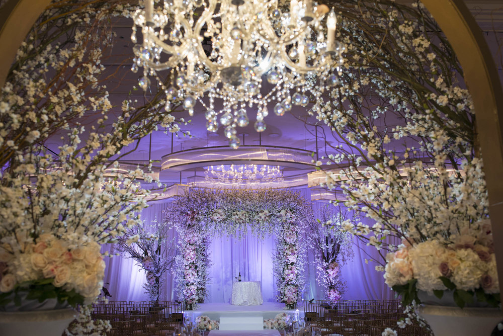 Over the top wedding ceremony featuring a 10X10 ft. chuppah, chandeliers, and cherry blossoms.  CREATIVE PARTNERS: PHOTOGRAPHY • AltF Photography, PLANNING • Andrea Eppolito Events, FLORAL AND DECOR DESIGN •Destinations by Design, VENUE AND CATERING • Mandarin Oriental, Las Vegas, STATIONERY DESIGN • Paper and Home, BRIDE'S GOWN • Vera Wang, SHOES • Jimmy Choo, GROOM'S FORMAL WEAR • Vera Wang, ENGAGEMENT RING • Delage Jewelers, WEDDING BANDS • T-Birds Jewels, CAKE DESIGN • Mandarin Oriental Las Vegas, DRAPING; DANCE FLOOR DESIGN AND PRODUCTION • Destination by Design, LIVE EVENT ARTIST • Sam Day, ENTERTAINMENT • Lucky Devils Band, CINEMATOGRAPHY • Something New