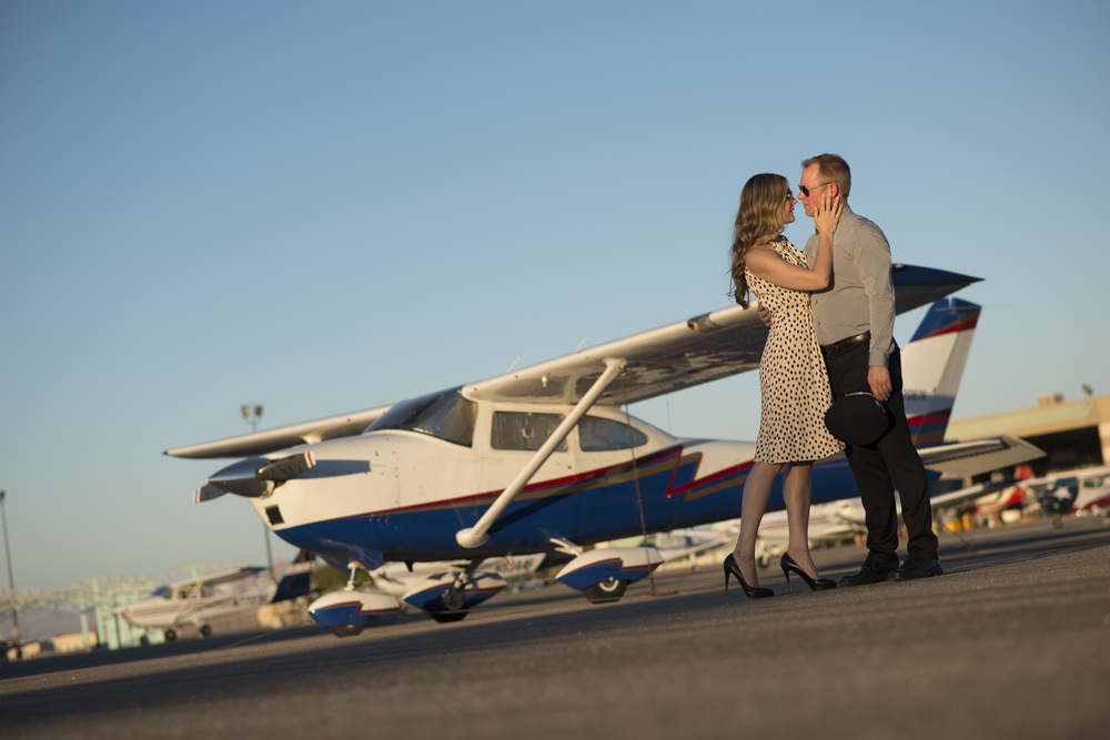 Destination Wedding Planner Andrea Eppolito | Engagement Photos in an Airplane Hanger | Images by AltF Photography | Kissing near plane