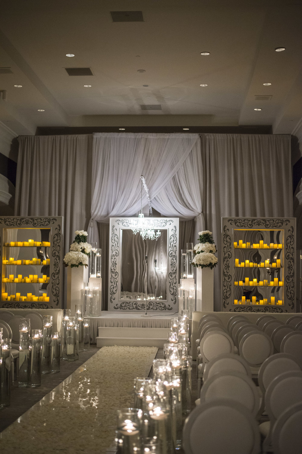White on white wedding with a large mirror and chandeliers.  Wedding by Las Vegas Wedding Planner Andrea Eppolito. Wedding at Four Seasons Las Vegas.    Image by AltF Photography.