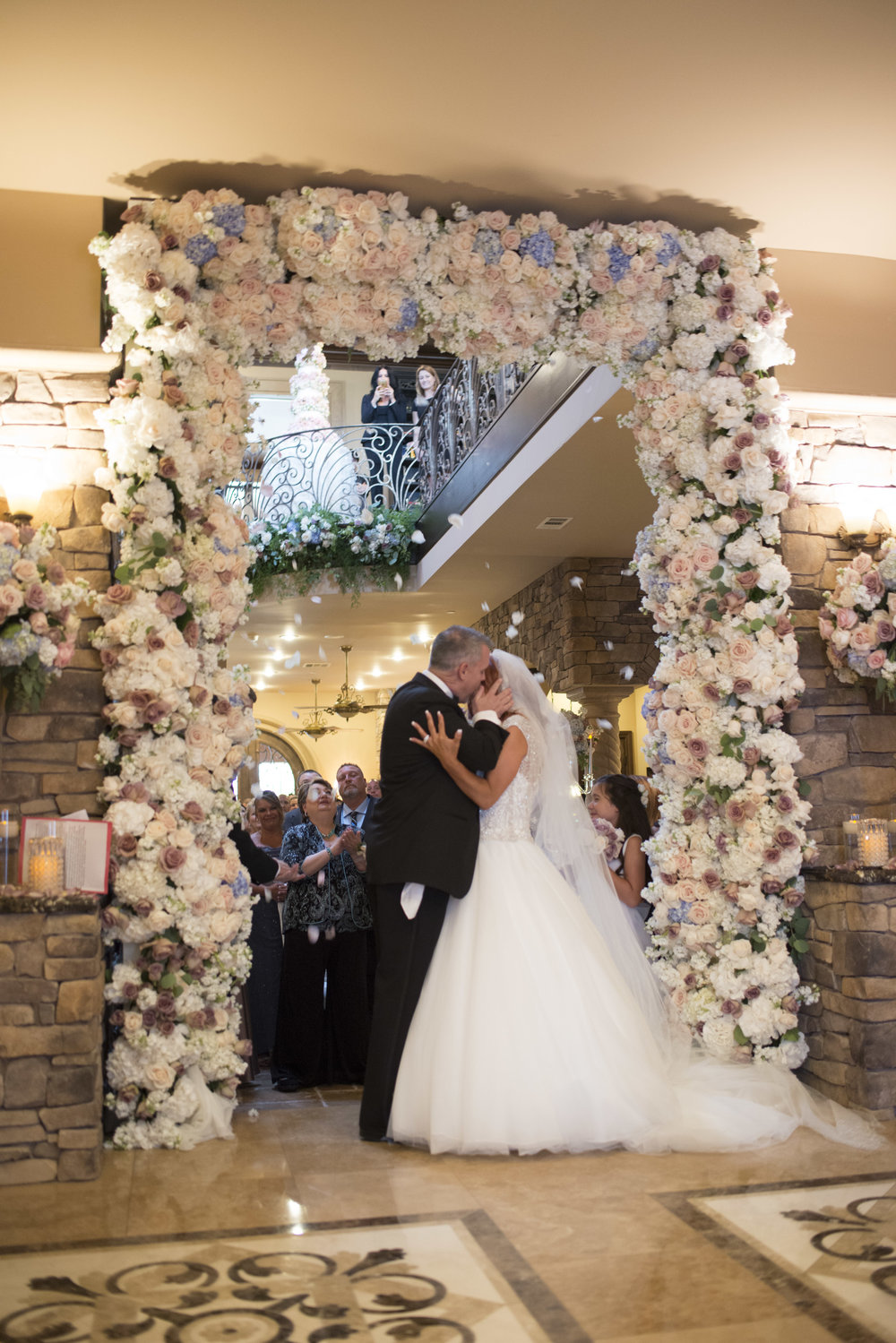 First Kiss with guests in the background. Luxury Las Vegas Wedding Planner Andrea Eppolito.  Image by AltF Photography.