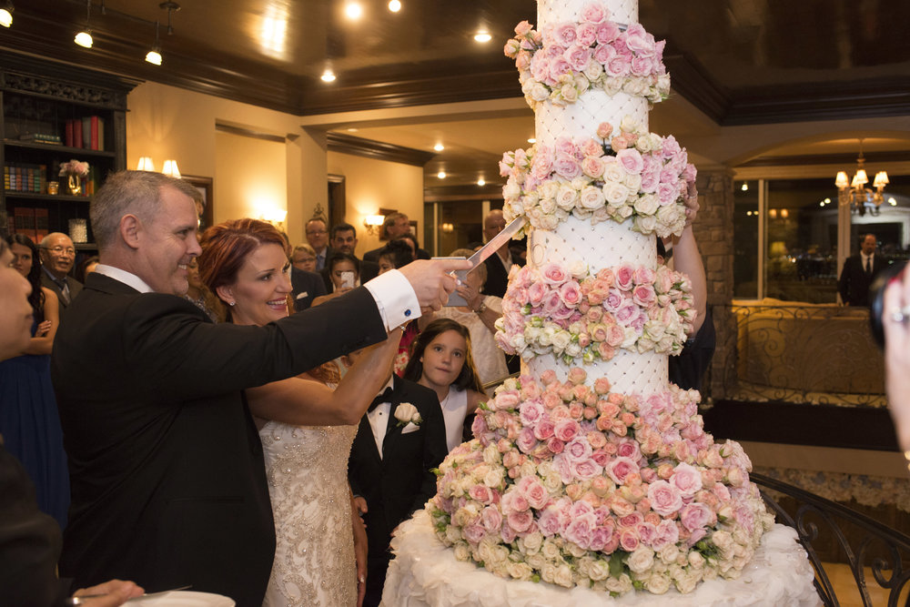 Bride and groom cut a 6 foot and 9 tier wedding cake. Luxury Las Vegas Wedding Planner Andrea Eppolito.  Image by AltF Photography.