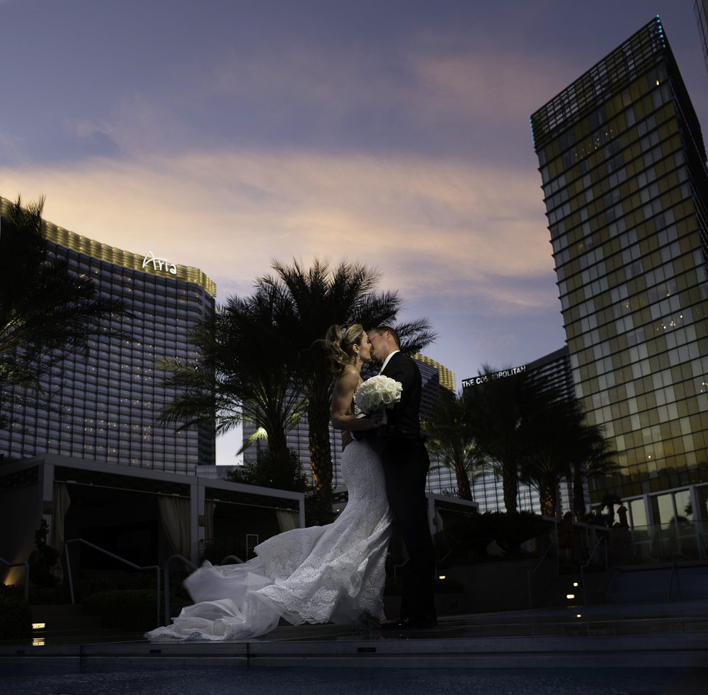 Bride and groom on bridge over the pool at the Mandarin Oriental.  Windy Wedding Photos.  Las Vegas Wedding Planner Andrea Eppolito.  Image by AltF.