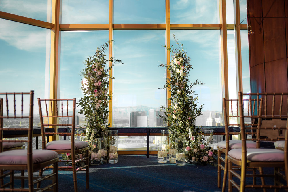 Wedding ceremony with two large floral sculptures.   Red and fuchsia bridal bouquet for wedding reception.    Styled Wedding Shoot inspired by French Blue.    Las Vegas Wedding Planner  Andrea Eppolito .  Photography by   Rebecca Marie  .  Floral and Decor by   By Dzign  .  Beauty by   Amelia C & Co  .  Shot at Rivea at The Delano.