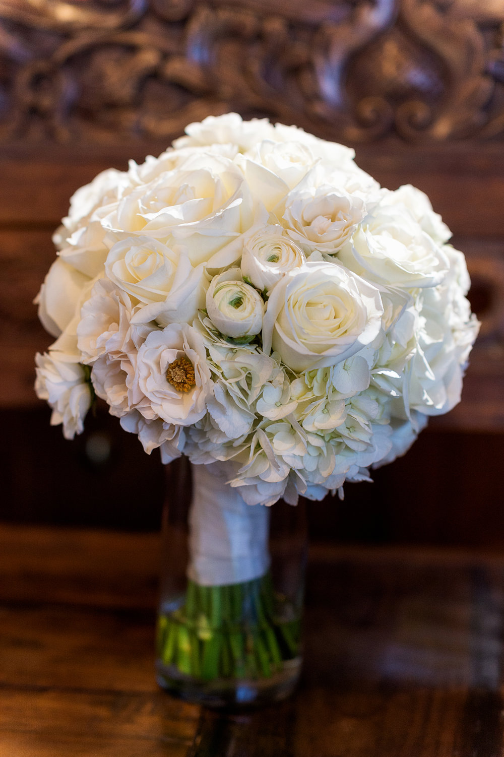 The bride's carried a classic white on white hand tied bouquet with ivory ribbon.  Roses, hydrangea, and ranuculous gave us gorgeous texture.  Bouquet by Naakiti Floral. Las Vegas Wedding Planner Andrea Eppolito.  Photo by Studio JK.