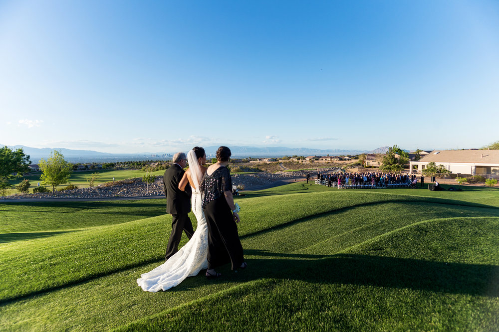 Bride being walked down the aisle by both parents.  Las Vegas Wedding Planner Andrea Eppolito.  Photo by Studio JK.