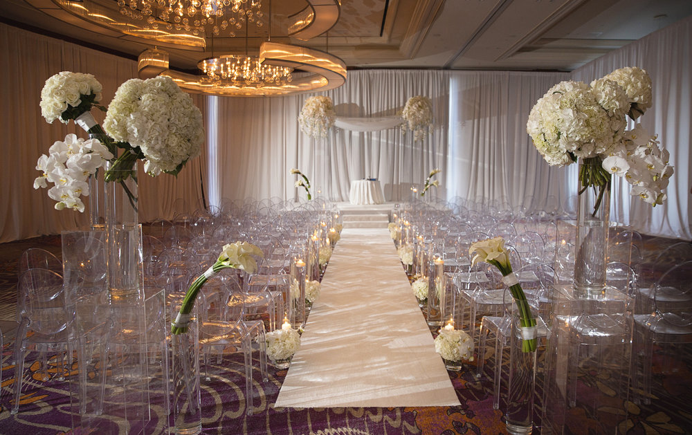 White on white modern wedding ceremony at The Mandarin Oriental.  Acrylic chuppah with candles against white drape. WEDDING PLANNING & EVENT DESIGN •  Andrea Eppolito Events , PHOTOGRAPHY •  AltF Photography ,  FLORAL AND DECOR DESIGN & PRODUCTION • Destinations by Design , CATERING •  Mandarin Oriental Las Vegas , COCKTAILS •  The Grand Bevy , WEDDING GOWN •  Galia Lahav ,  SHOES •  Jimmy Choo