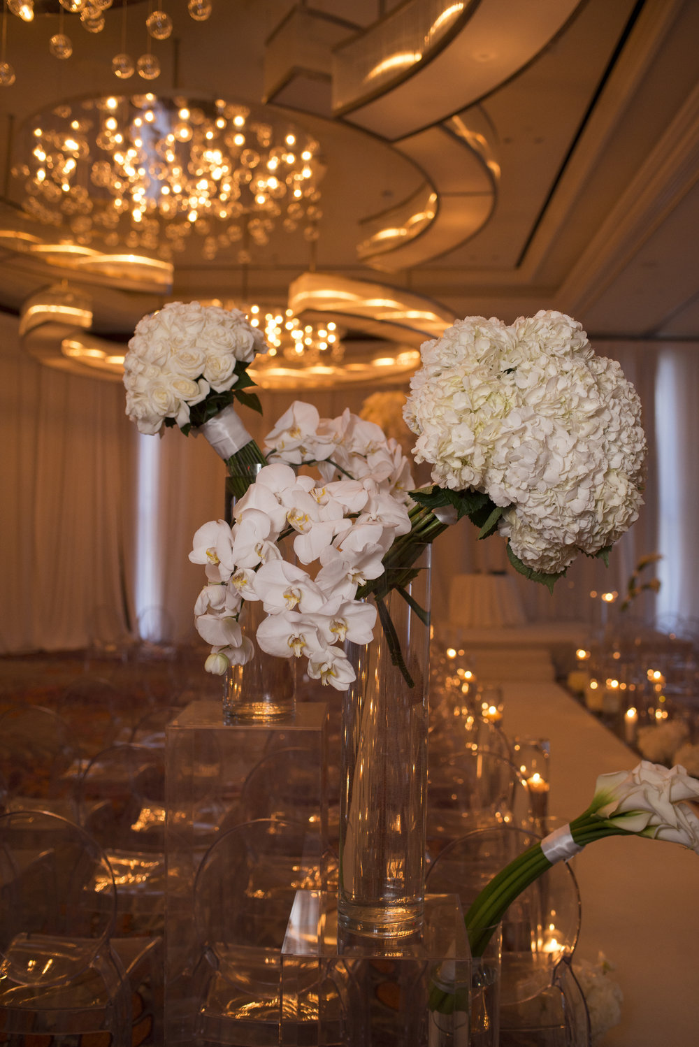 White and ivory flowers in acrylic and glass vases.  WEDDING PLANNING & EVENT DESIGN •  Andrea Eppolito Events , PHOTOGRAPHY •  AltF Photography ,  FLORAL AND DECOR DESIGN & PRODUCTION • Destinations by Design , CATERING •  Mandarin Oriental Las Vegas , COCKTAILS •  The Grand Bevy , WEDDING GOWN •  Galia Lahav ,  SHOES •  Jimmy Choo