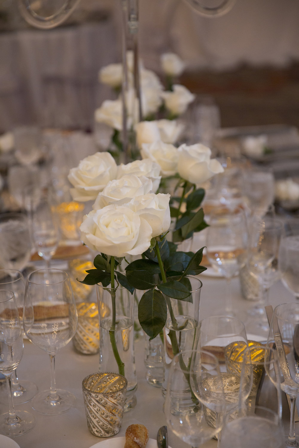 White roses in clear bud vases. WEDDING PLANNING & EVENT DESIGN •  Andrea Eppolito Events , PHOTOGRAPHY •  AltF Photography ,  FLORAL AND DECOR DESIGN & PRODUCTION • Destinations by Design , CATERING •  Mandarin Oriental Las Vegas , COCKTAILS •  The Grand Bevy , WEDDING GOWN •  Galia Lahav ,  SHOES •  Jimmy Choo , ACRYLIC MENUS & SEATING CHART•  She Paperie