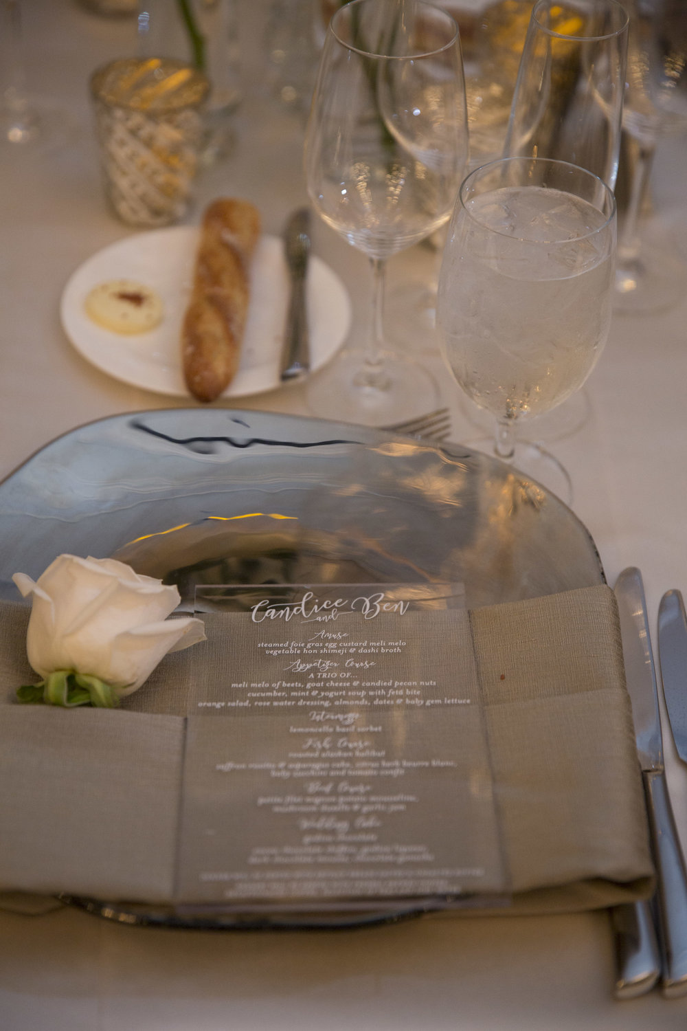 Acrylic menus with white etched lettering.  A white rose on each napkin. WEDDING PLANNING & EVENT DESIGN •  Andrea Eppolito Events , PHOTOGRAPHY •  AltF Photography ,  FLORAL AND DECOR DESIGN & PRODUCTION • Destinations by Design , CATERING •  Mandarin Oriental Las Vegas , COCKTAILS •  The Grand Bevy , WEDDING GOWN •  Galia Lahav ,  SHOES •  Jimmy Choo , ACRYLIC MENUS & SEATING CHART•  She Paperie