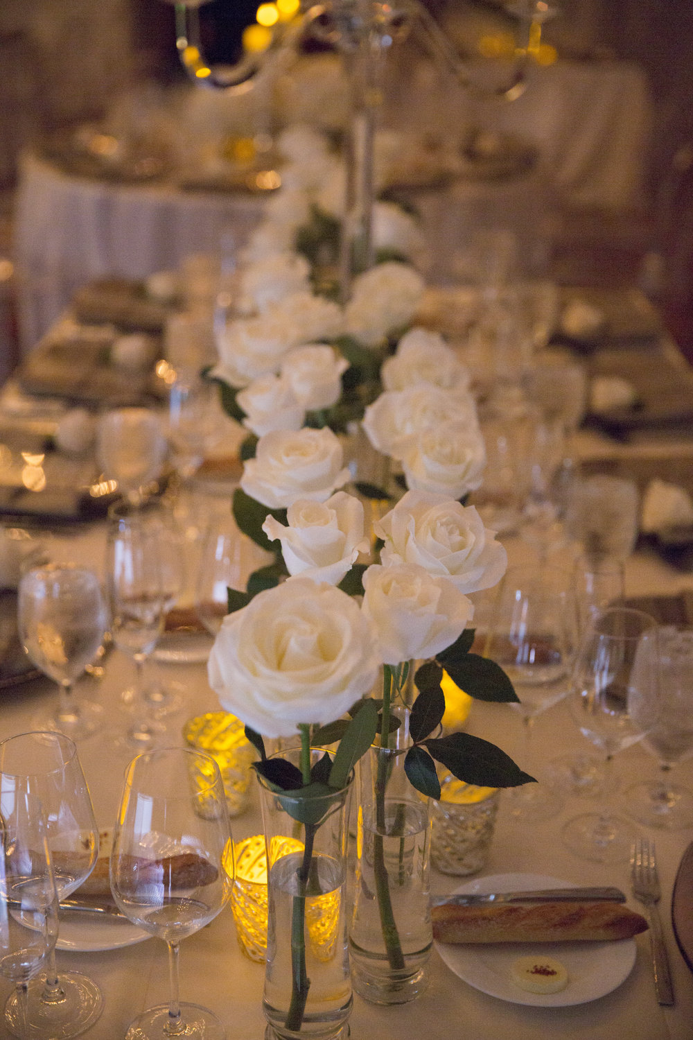 Bold white roses in straight line on long wedding table.  WEDDING PLANNING & EVENT DESIGN •  Andrea Eppolito Events , PHOTOGRAPHY •  AltF Photography ,  FLORAL AND DECOR DESIGN & PRODUCTION • Destinations by Design , CATERING •  Mandarin Oriental Las Vegas , COCKTAILS •  The Grand Bevy , WEDDING GOWN •  Galia Lahav ,  SHOES •  Jimmy Choo , ACRYLIC MENUS & SEATING CHART•  She Paperie