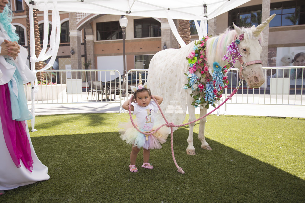 Birthday girl takes unicorn for a birthday walk. Celebrity Event Planner Andrea Eppolito.  Floral and Rentals by Destinations by Design. Photo by Triple Vision Studios.