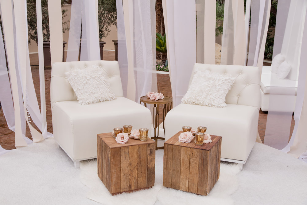 White club chairs and wooden tables at upscale wedding in Las Vegas.  Destination Wedding Planner  Andrea Eppolito  · Photos by  Adam Frazier Photography  · Floral and Decor by  Destinations by Design  ·  Lighting by  LED Unplugged  · Venue  · Invitations  Ceci New York   ·  Menus by  Alligator Soup