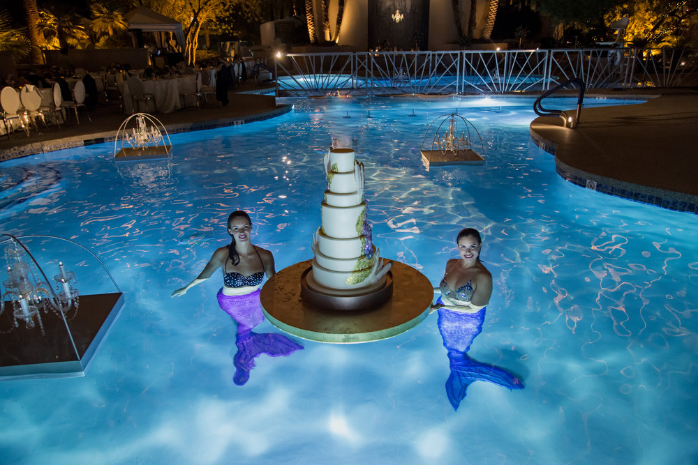 Mermaids brought the wedding cake to the edge of the pool so it could be cut.  Destination Wedding Planner  Andrea Eppolito  · Photos by  Adam Frazier Photography  · Floral and Decor by  Destinations by Design  ·  Lighting by  LED Unplugged  · Venue  · Invitations  Ceci New York   ·  Menus by  Alligator Soup