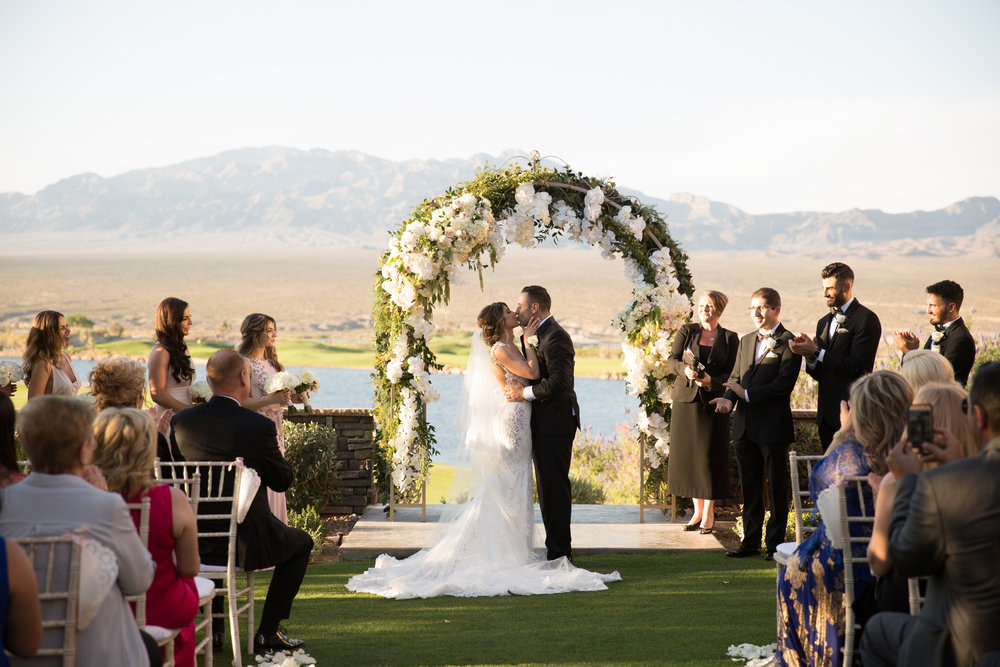 First Kiss at roamntic outdoor wedding.  Luxury Destination Wedding Planning and Event Design by  Andrea Eppolito Events  · Photos by  Stephen Salazar  · Flowers by  Naakiti Floral  ·  Rentals by RSVP · Lighting by  LED Unplugged   · Venue  Paiute Golf Course .  Dress by  Berta  · Shoes by  Jimmy Choo