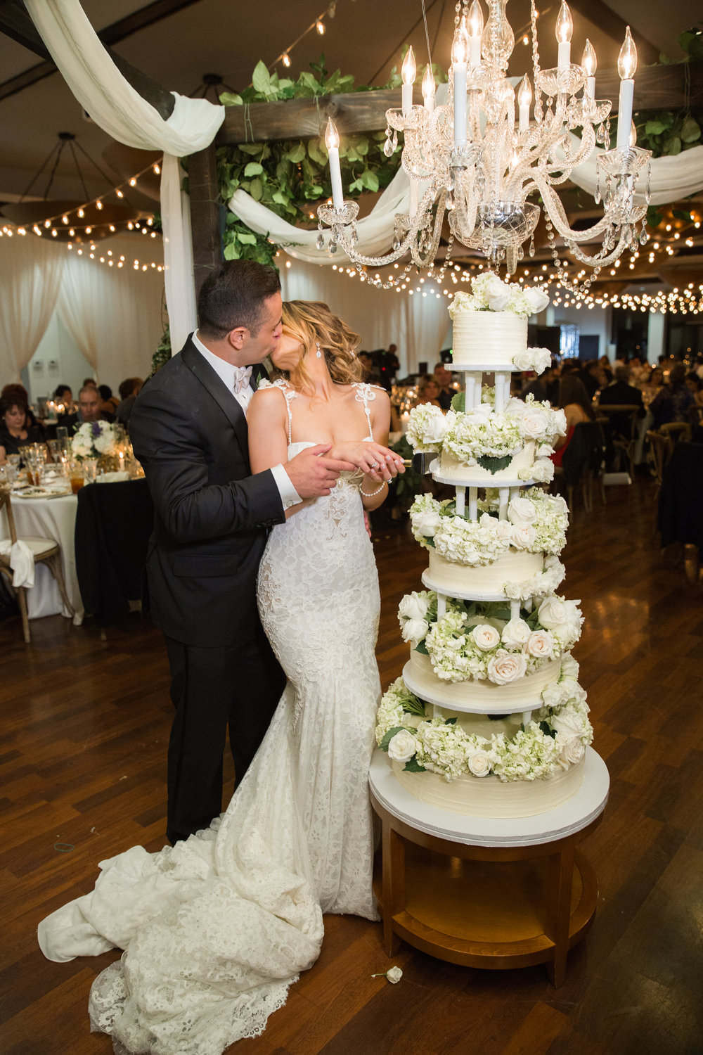 Cutting the cake and kisses.  Luxury Destination Wedding Planning and Event Design by  Andrea Eppolito Events  · Photos by  Stephen Salazar