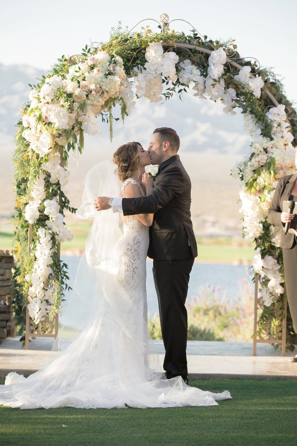 First kiss under a white and green arch  |   Luxury Destination Wedding Planning and Event Design by  Andrea Eppolito Events  · Photos by  Stephen Salazar