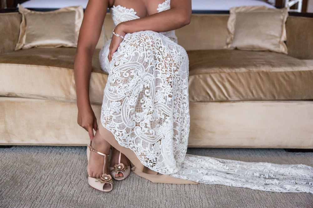 Bride putting on shoes with her lace Berta gown.  Wedding Planning by  Andrea Eppolito Events   ·  Photography by  Shandro Photo    ·  Wedding Venue  Four Seasons Las Vegas   ·  Floral and Decor by  Destination by Design   ·  Chandeliers and Lighting by  LED Unplugged